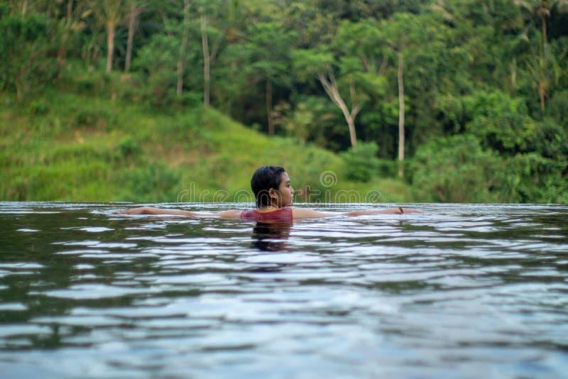 Natación asiática joven de la muchacha en la piscina del infinito con hermosa vista Le toman las fotos de la parte posterior foto de archivo