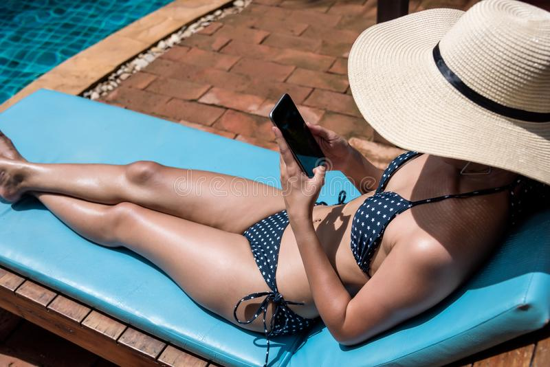 Natación cercana relajante de la muchacha de la mujer del smartphone feliz hermoso del uso fotos de archivo libres de regalías
