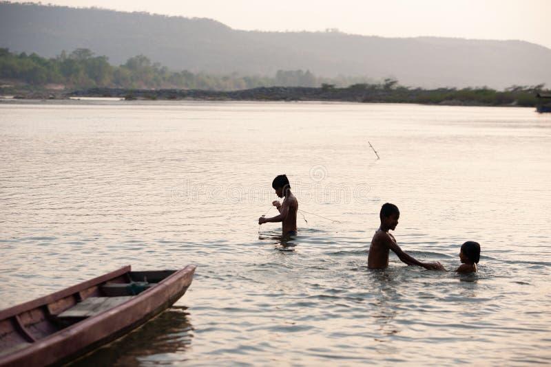 Natación de Bru Children de la tribu y el jugar en el río Mekong en summe imagen de archivo