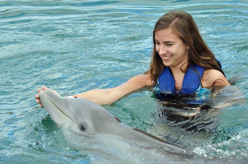 Natación de la muchacha con el delfín imagen de archivo libre de regalías