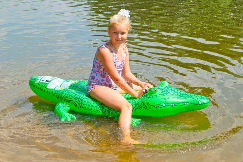 Natación de la muchacha en el río con el cocodrilo inflable imágenes de archivo libres de regalías