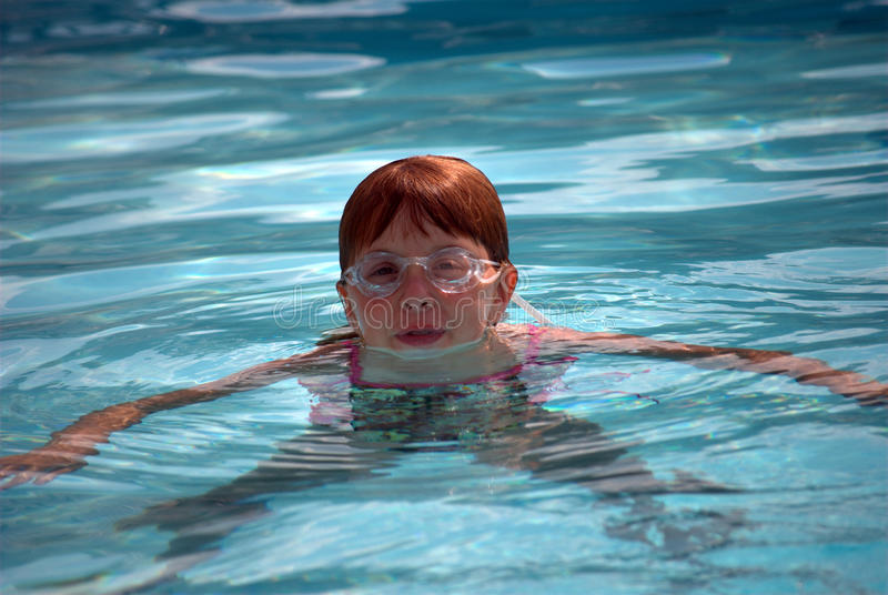 Natación de la muchacha en piscina foto de archivo