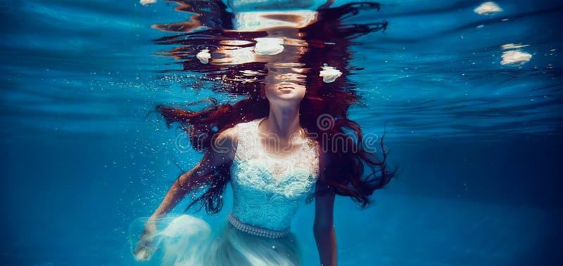 Natación de la muchacha subacuática imagen de archivo