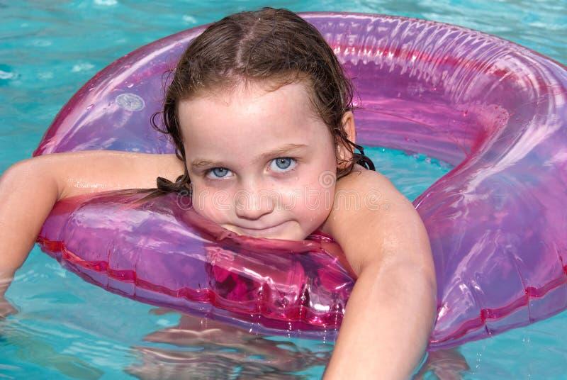 Natación de la niña en piscina con el flotador fotografía de archivo