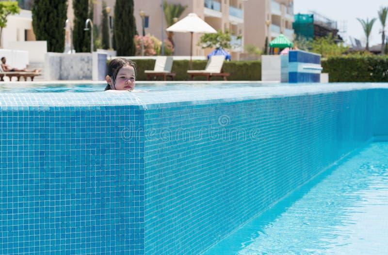 Natación de la niña en una piscina del aire abierto fotografía de archivo
