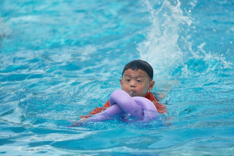 Natación de la práctica del muchacho con el flotador de la espuma de los tallarines fotos de archivo