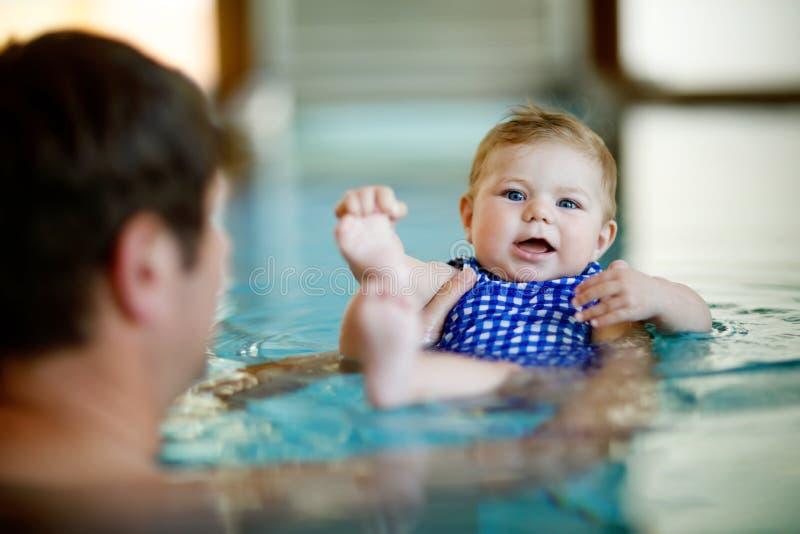 Natación de mediana edad feliz del padre con la hija adorable linda del bebé en piscina del giro Papá sonriente y pequeño niño, m imagen de archivo