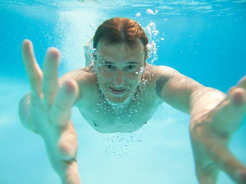 Natación del hombre bajo el agua imagen de archivo libre de regalías