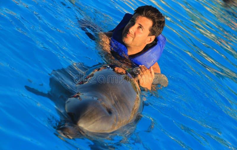 Natación del hombre de los ojos verdes con los delfínes felices sonrientes de la aleta magnífica del delfín de la cara del niño d fotos de archivo
