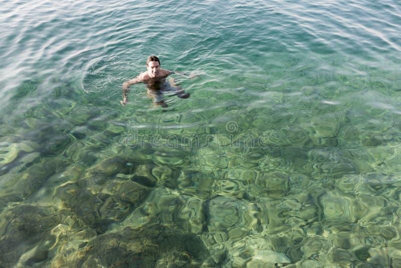 Natación del hombre en el mar fotos de archivo