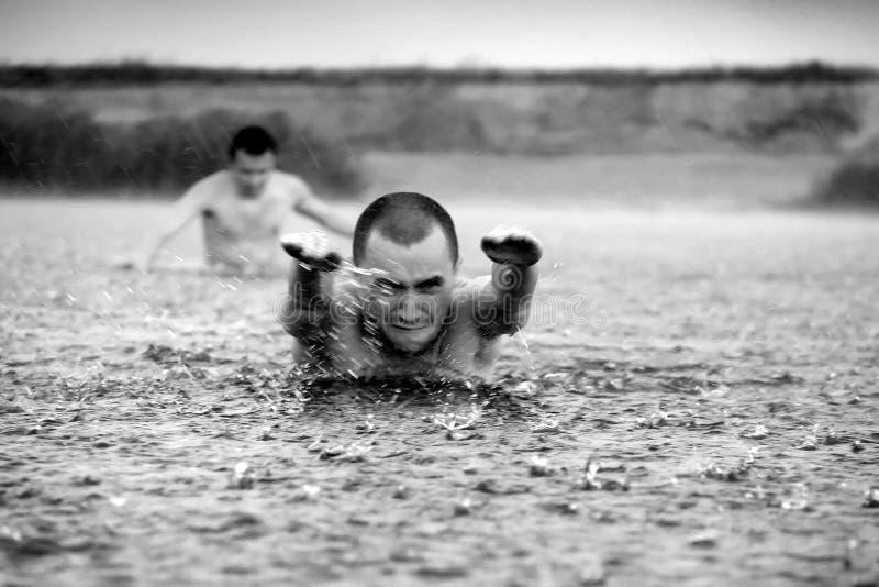 natación del hombre en la lluvia fotos de archivo libres de regalías