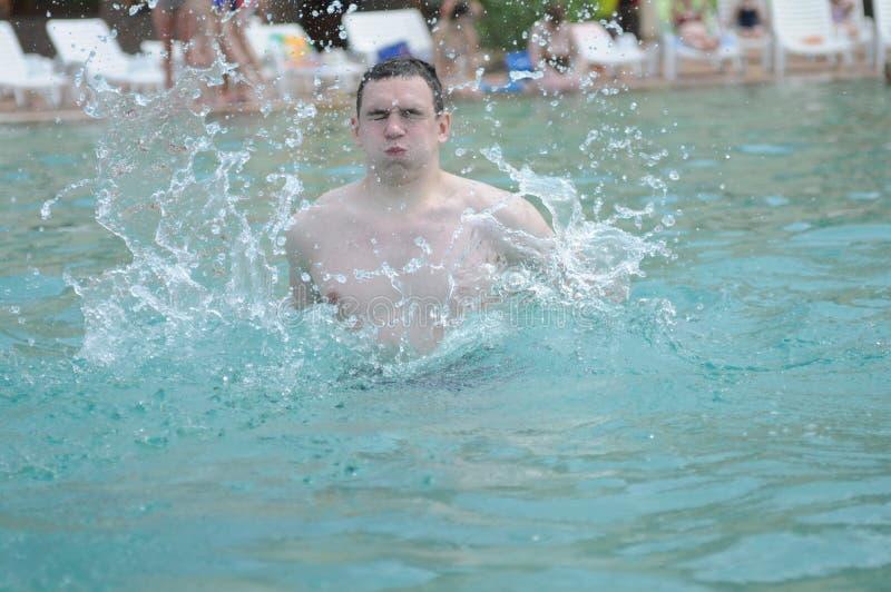 Natación del hombre joven en agua de los océanos Hombre atractivo en la playa en verano Varón hermoso con el cuerpo del ajuste, fotografía de archivo