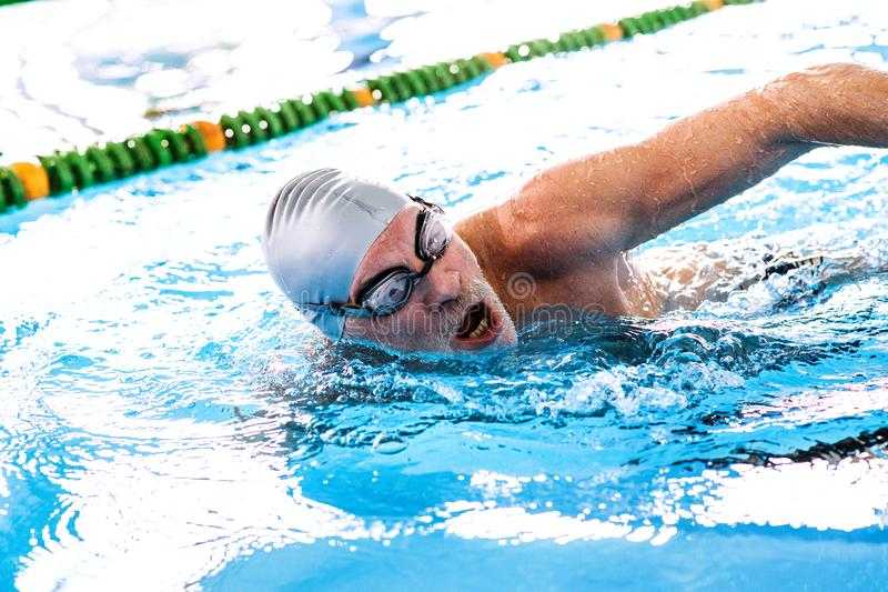 Natación del hombre mayor en una piscina interior fotos de archivo