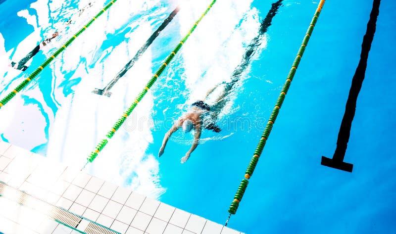 Natación del hombre mayor en una piscina interior imagen de archivo libre de regalías