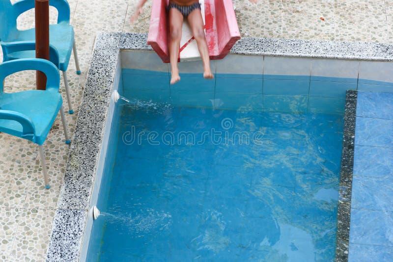 Natación del niño en la piscina imagenes de archivo