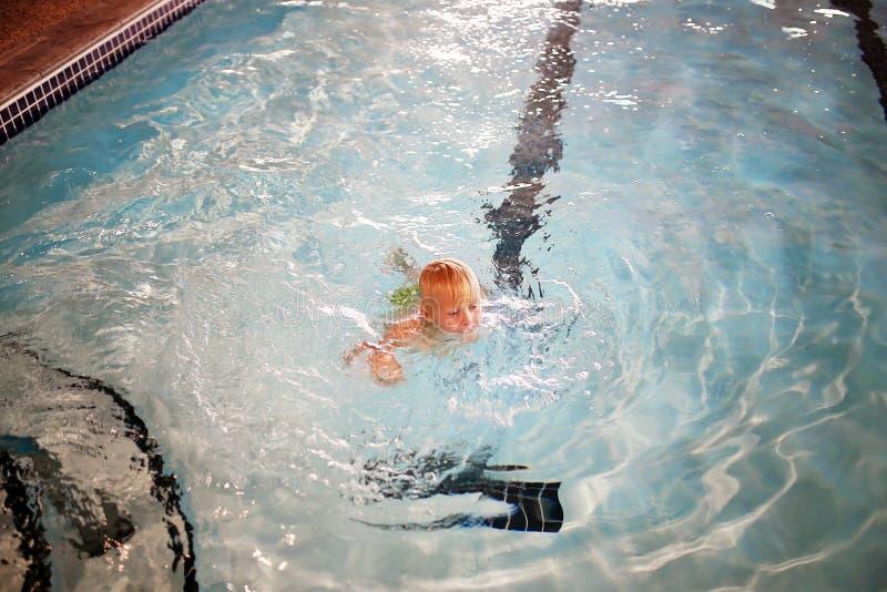 Natación del niño joven en piscina interior en el hotel fotografía de archivo libre de regalías