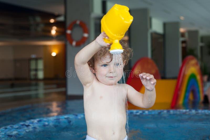 Natación del niño pequeño, divirtiéndose y jugando en agua imágenes de archivo libres de regalías