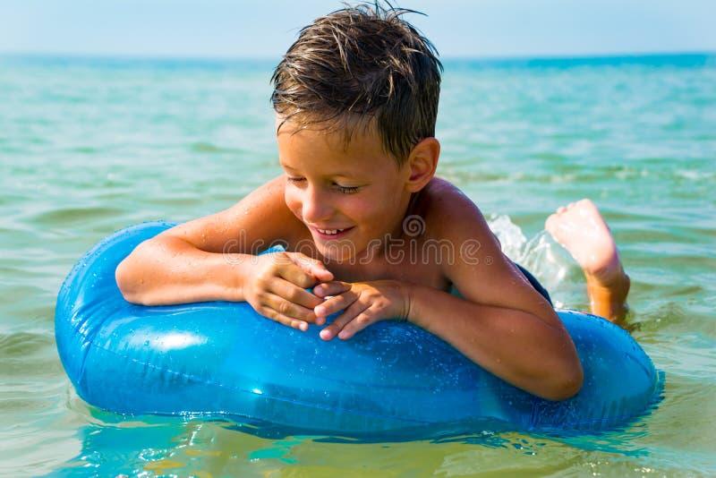 Natación del niño pequeño en el mar con el anillo de goma fotografía de archivo libre de regalías