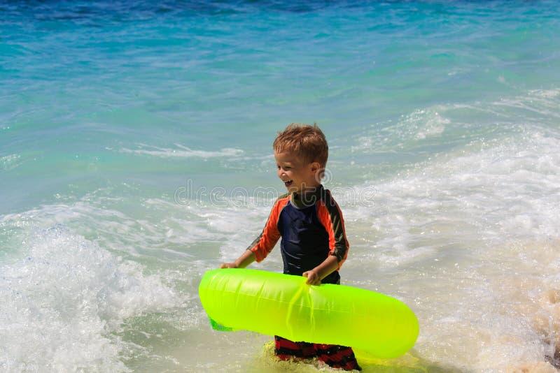 Natación del niño pequeño en la playa foto de archivo