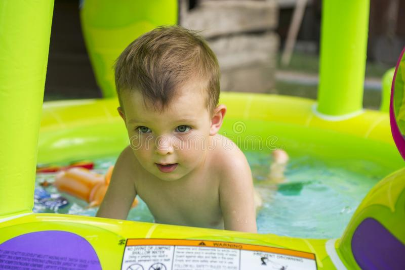 Natación feliz del bebé en piscina inflable del niño en césped fotos de archivo libres de regalías