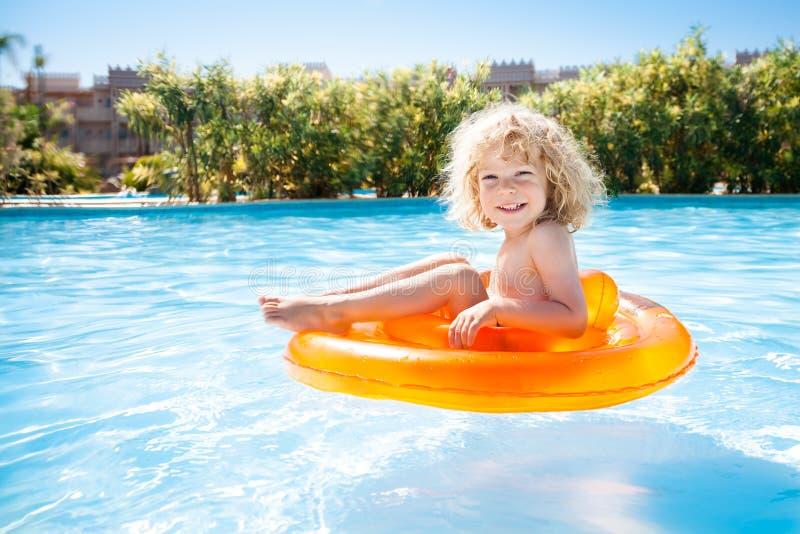 Natación feliz del cabrito en piscina fotografía de archivo