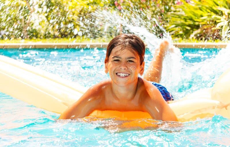 Natación feliz del muchacho en el colchón de aire en piscina al aire libre fotografía de archivo