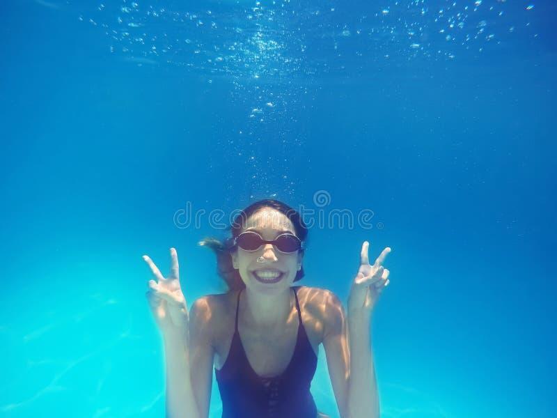 Natación hermosa de la mujer joven en piscina imagen de archivo libre de regalías