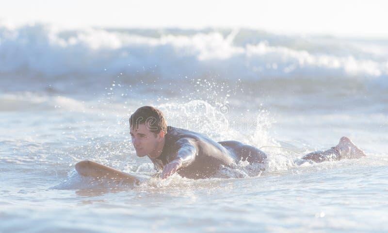 Natación joven de la persona que practica surf en el océano y el conseguir listo para coger el th imagenes de archivo