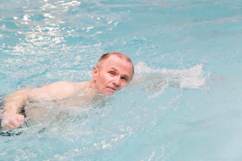 Natación masculina de Senoir en piscina interior fotografía de archivo