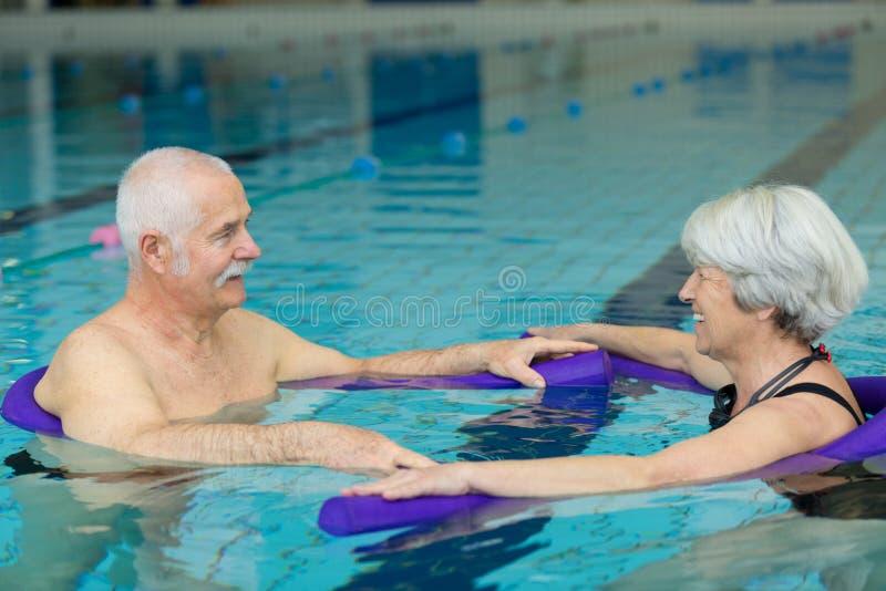 Natación mayor feliz de los pares en piscina imagenes de archivo