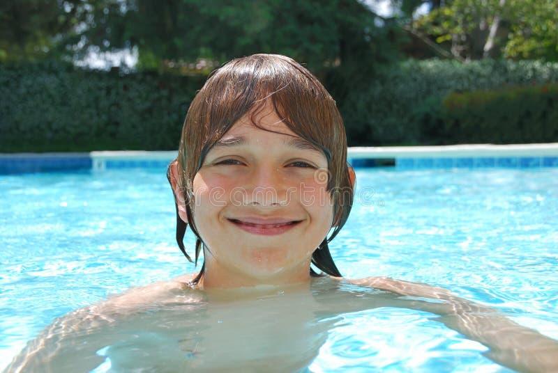 Natación sonriente del adolescente en piscina imagen de archivo