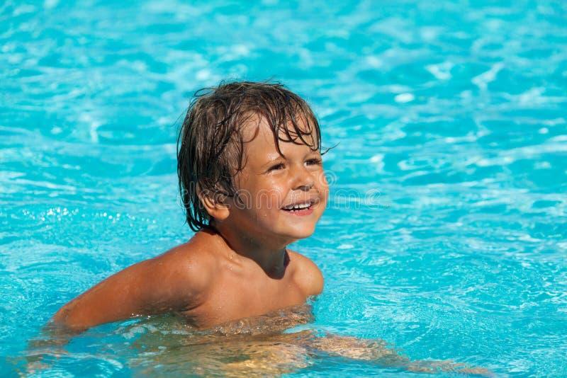 Natación sonriente del muchacho en piscina y la mirada fotografía de archivo