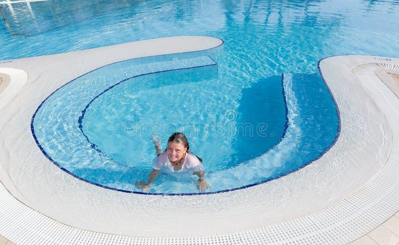 natación sonriente feliz de la niña y relajación en la piscina con agua cristalina fotografía de archivo libre de regalías