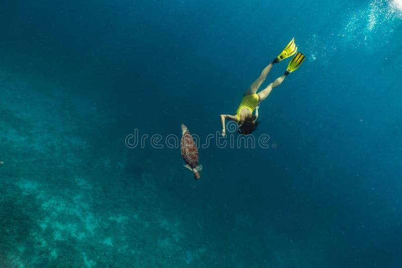 Natación subacuática de la muchacha caucásica con la tortuga en el mar azul imagenes de archivo
