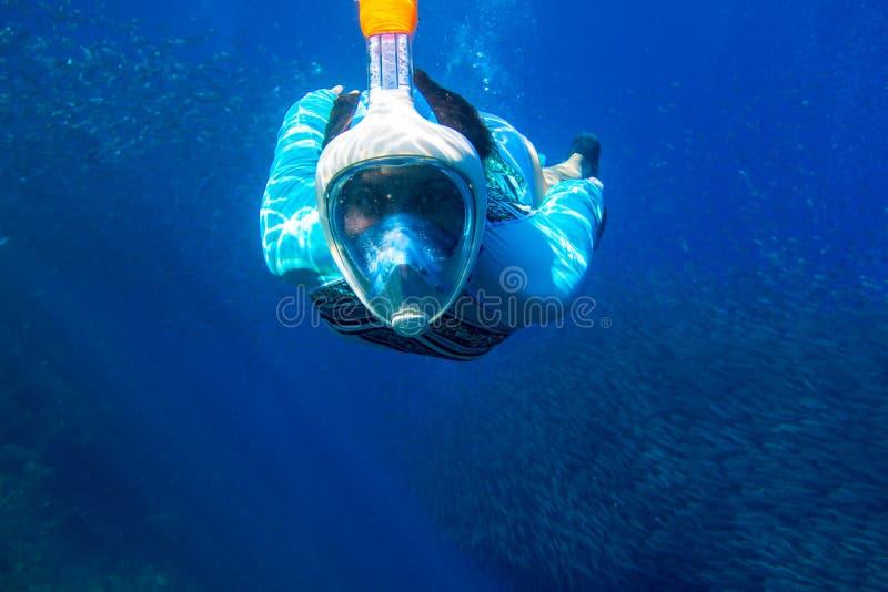 Nataci?n de la mujer en el mar azul Muchacha que bucea en máscara de la lleno-cara Tubo respirador con la foto subacuática de la  fotografía de archivo libre de regalías