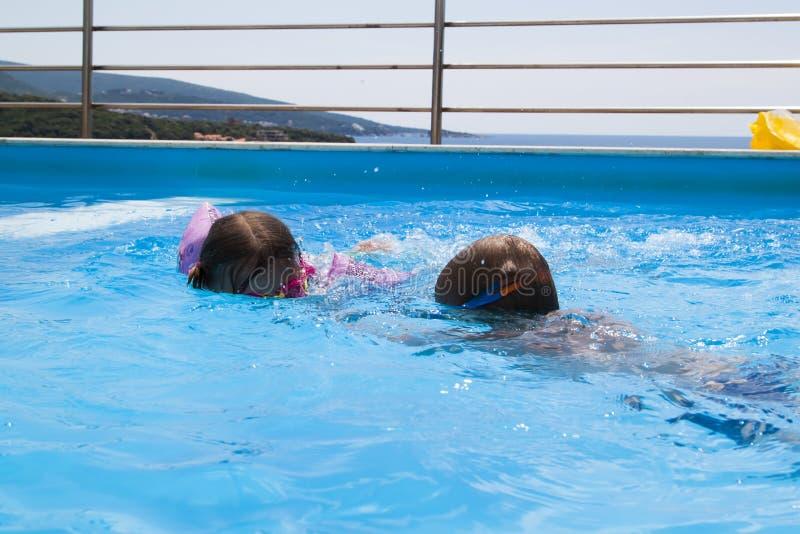 nataci?n del muchacho y de la muchacha en la piscina en el chalet fotografía de archivo