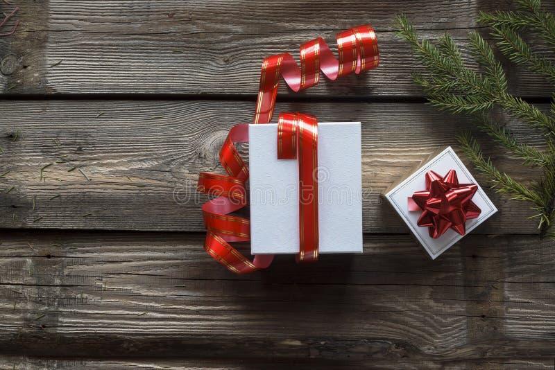 Natal, ano novo branco, caixa de presente, fita vermelha, fundo de madeira, vista superior, vintage, espaço para o texto Entrega  fotografia de stock