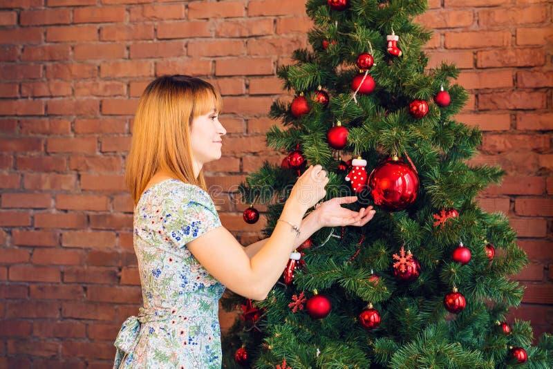 Natal, decoração, feriados e conceito dos povos - a mulher decora a árvore de Natal imagem de stock royalty free