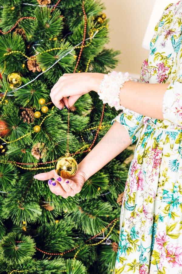 Natal, decoração, feriados e conceito dos povos - próximo acima da mão da mulher que guarda a bola do ouro do Natal imagem de stock royalty free