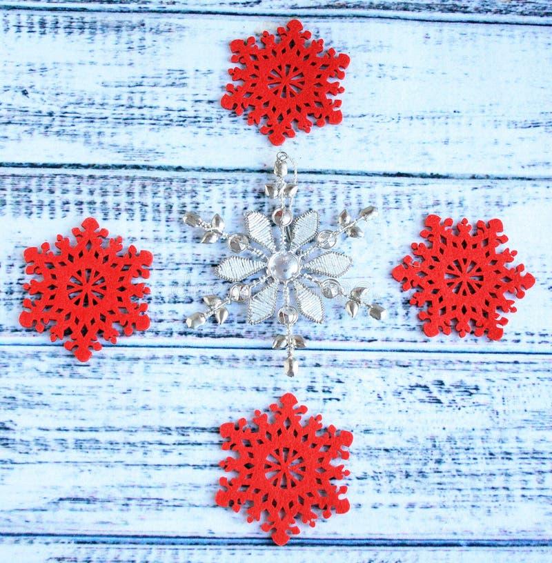 Natal do floco da neve do metal e dos quatro flocos da neve do vermelho em um branco a imagens de stock royalty free