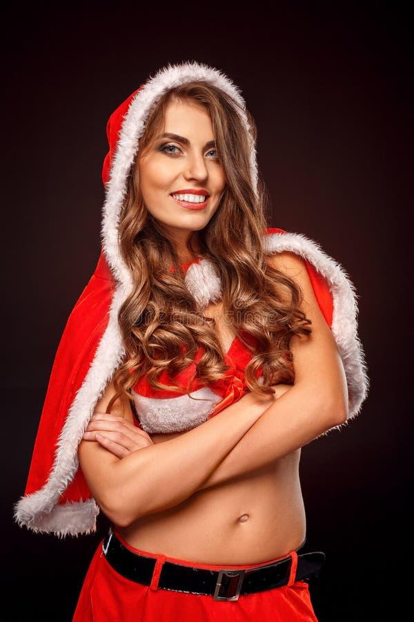 Natal e ano novo Mulher no traje de Santa com posição da capa no sorriso cruzado preto dos braços alegre fotos de stock