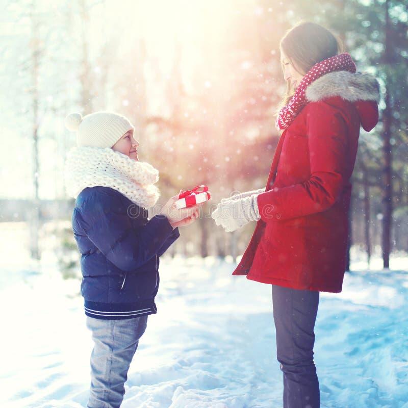 Natal, família e conceito do inverno - o filho feliz da criança dá a caixa de presente da mãe no inverno ensolarado fotografia de stock