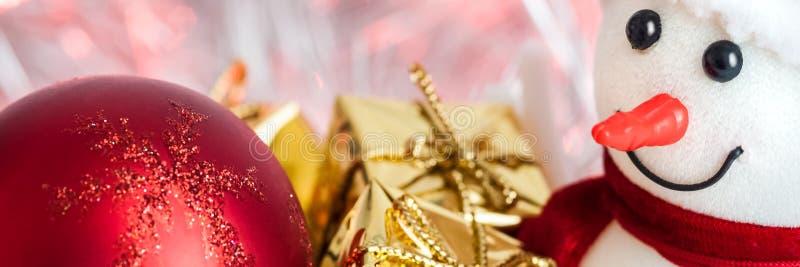 Natal feliz, ano novo, boneco de neve, presentes em umas caixas do ouro e bolas vermelhas em um fundo cor-de-rosa do bokeh imagem de stock royalty free