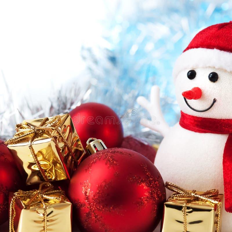 Natal feliz, ano novo, boneco de neve, presentes em umas caixas douradas e bolas vermelhas em um fundo azul e branco do bokeh imagem de stock royalty free