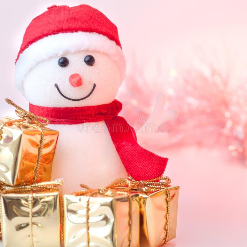 Natal feliz, ano novo, boneco de neve, presentes em umas caixas douradas em um fundo do rosa e bokeh amarelo fotos de stock