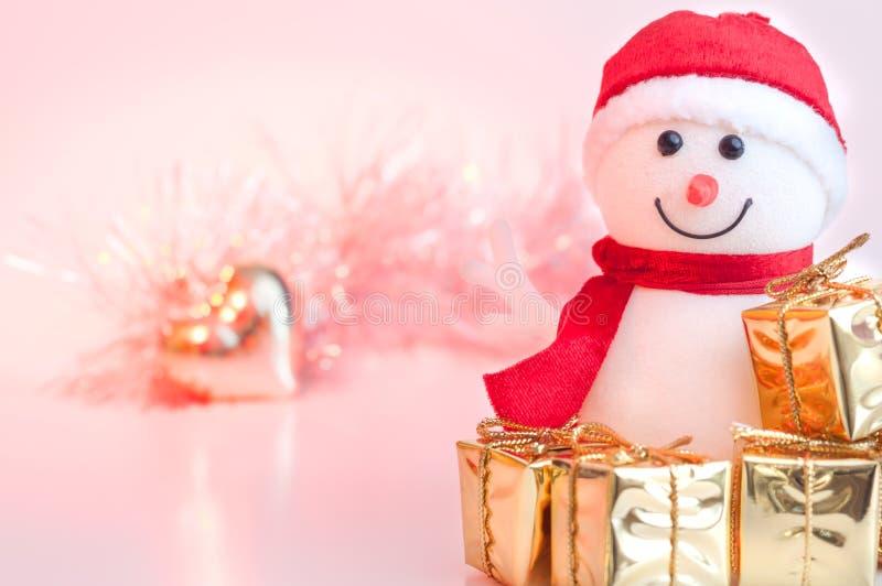 Natal feliz, ano novo, presentes do boneco de neve em umas caixas douradas e um coração dourado em um fundo do rosa e do bokeh am fotografia de stock royalty free