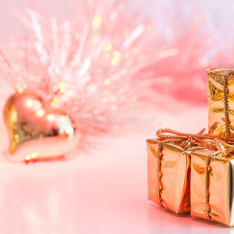 Natal feliz, ano novo, presentes em umas caixas do ouro e um coração dourado em um fundo do rosa e do bokeh amarelo fotos de stock royalty free