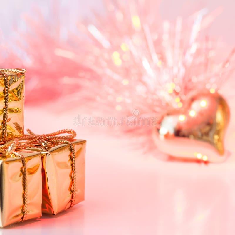 Natal feliz, ano novo, presentes em umas caixas do ouro e um coração dourado em um fundo do rosa e do bokeh amarelo imagens de stock royalty free