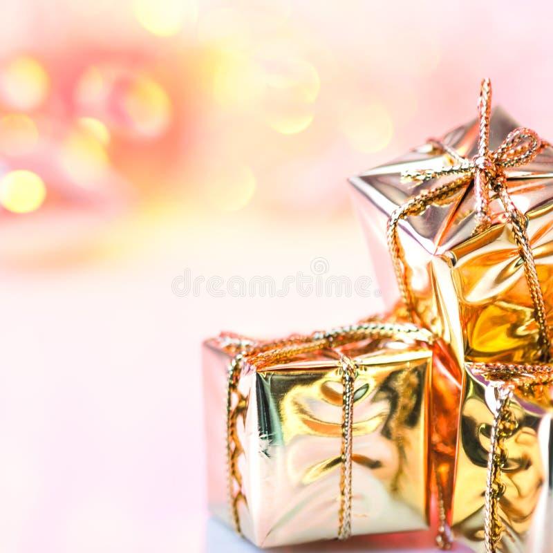 Natal feliz, ano novo, presentes em umas caixas do ouro em um fundo do rosa e bokeh amarelo imagem de stock royalty free