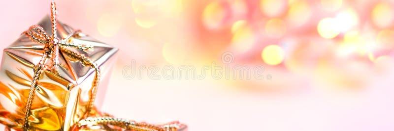 Natal feliz, ano novo, presentes em umas caixas do ouro em um fundo do rosa e bokeh amarelo fotos de stock royalty free